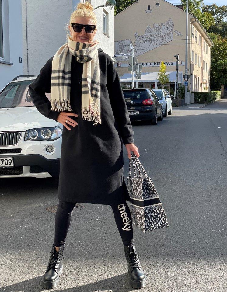 Renate Zott im Athleisure Wear-Look 1: ein schwarzes Sweatkleid mit Kapuze über der Sportkleidung...